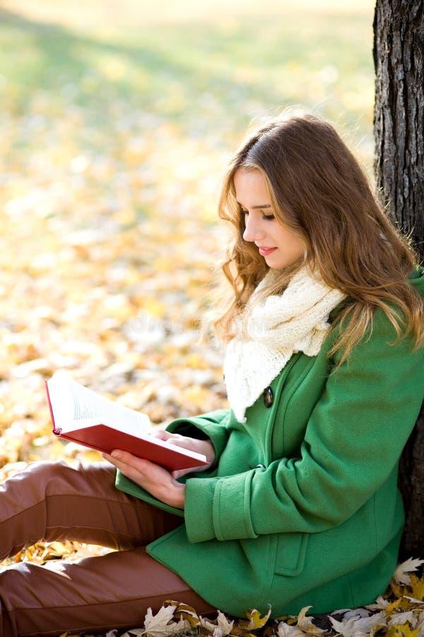 bokflicka som läser utomhus royaltyfri fotografi