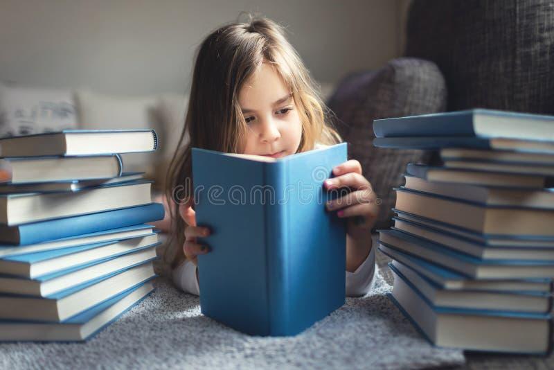 bokflickan läser barn arkivfoto