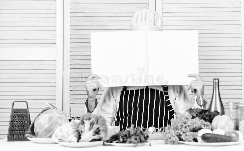 Bokrecept kopierar utrymme Mankocken i hatt och f?rkl?de l?ste boken Kulinariska recept bokar begrepp F?rb?ttra att laga mat expe royaltyfria bilder