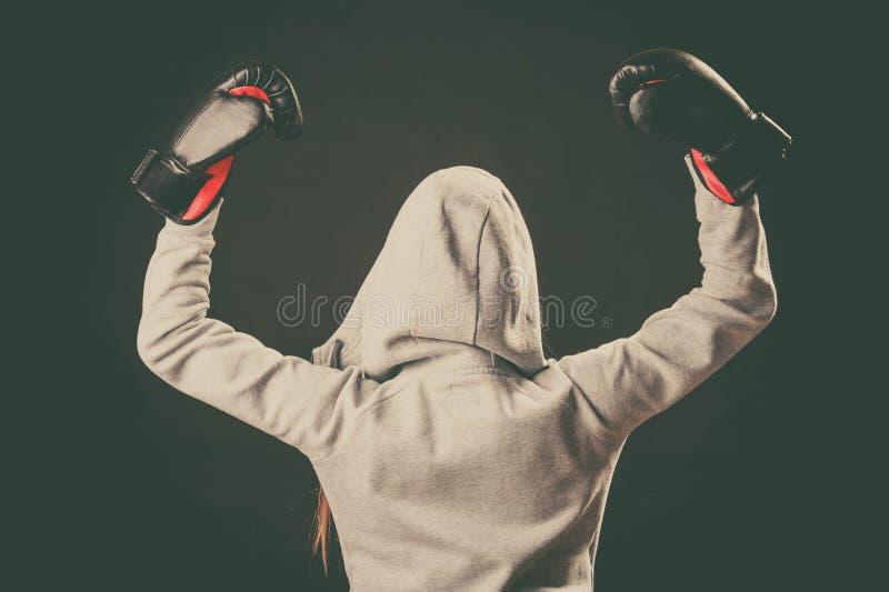 Bokser in hoodietribune achteruit met wapens in lucht stock foto