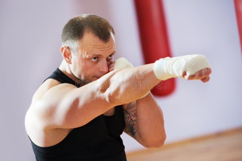 Boksera mężczyzna przy bokserskim szkoleniem z ciężką torbą obraz stock
