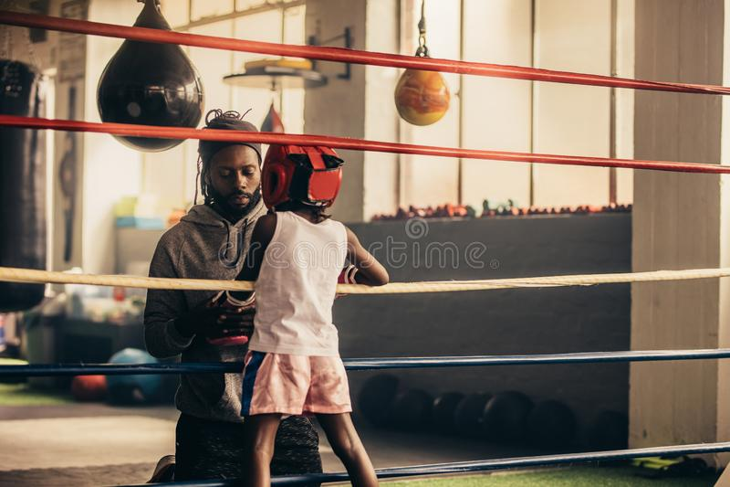 Bokserska dzieciak pozycja wśrodku pierścionku opowiada jego trener obrazy stock