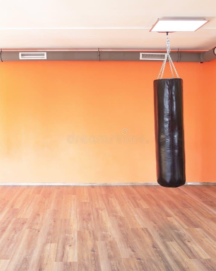 Bokserska nowożytna uderza pięścią torba na tle pomarańczowa ściana w nowym nowożytnym gym, kopii przestrzeń obraz stock