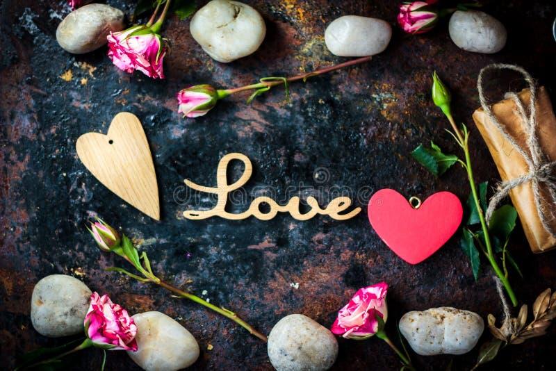 Bokstäver ÄLSKAR och valentins daghjärta och blommor arkivbild