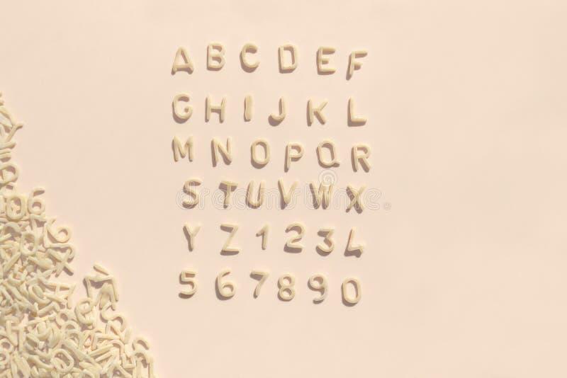 Bokstäver av alfabetet av pasta för ungemat på ljust - rosa bakgrund Pastellfärgad färg för barns mål royaltyfri fotografi