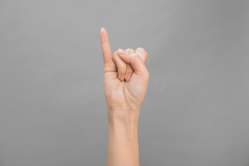 Bokstav för kvinnavisning I på grå bakgrund Teckenspråk arkivfoto