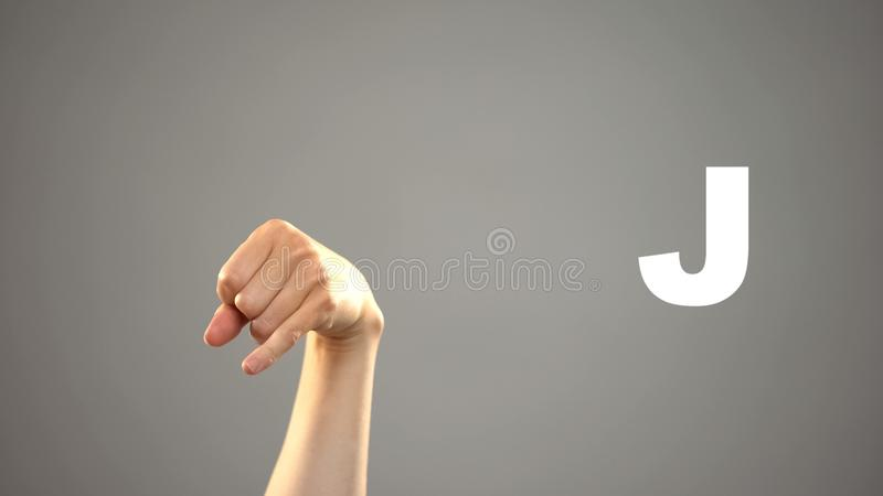 Bokstav J i teckenspr?ket, hand p? bakgrund, kommunikation f?r d?vt, kurs royaltyfri bild