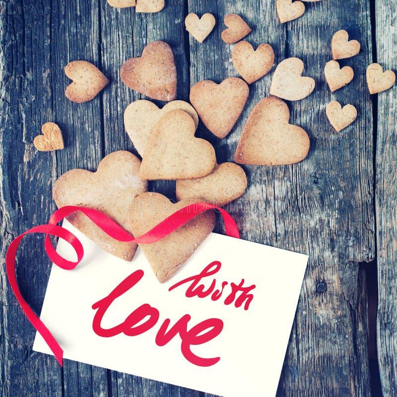 Bokstav med meddelandet med förälskelse och kakor på Valentine Day tonat royaltyfri bild