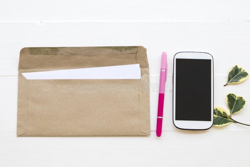 Bokstav mobiltelefon för affärsarbete på kontorsskrivbordet arkivfoto