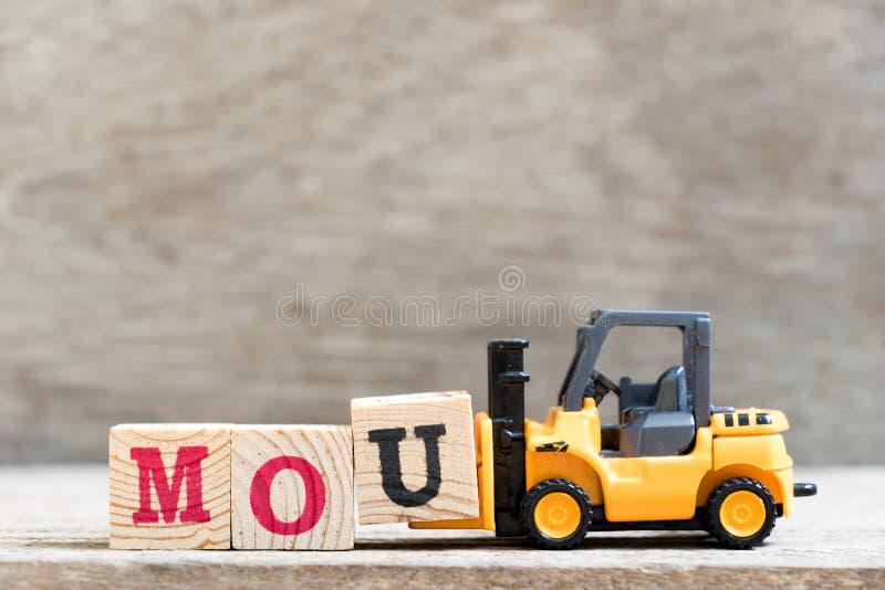 Bokstav u för leksakgaffeltruckhåll i ordmou-förkortning av anteckningen av överenskommelse på träbakgrund royaltyfria bilder