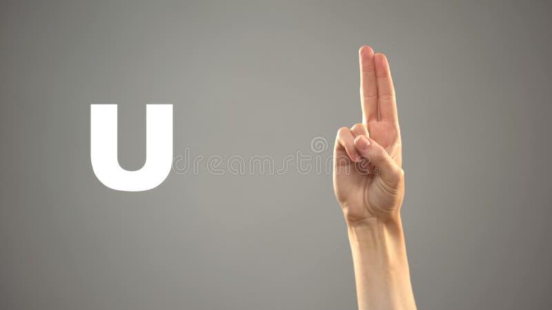 Bokstav U i teckenspr?ket, hand p? bakgrund, kommunikation f?r d?vt, kurs royaltyfri foto
