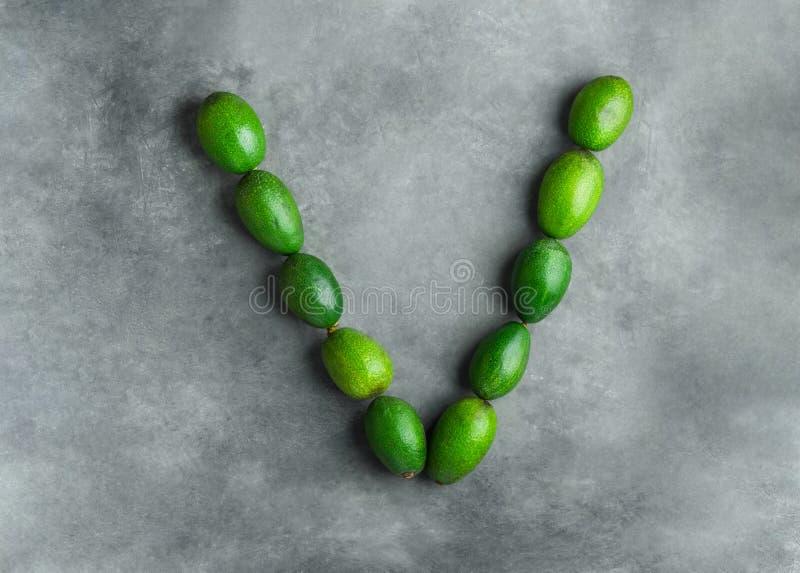 Bokstav V för vitaliteten för strikt vegetariangrönsakvitaminer som göras från mogna rå avokadon på mörkt - grå stenbakgrund Matt royaltyfria bilder