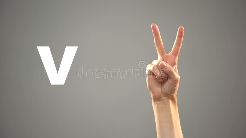 Bokstav V i teckenspr?ket, hand p? bakgrund, kommunikation f?r d?vt, kurs arkivfoton