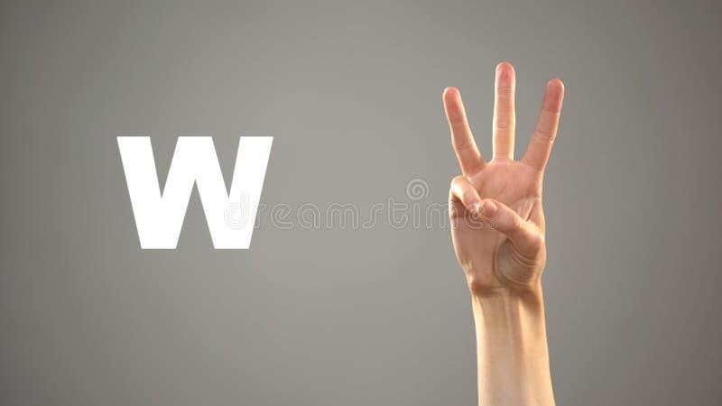 Bokstav W i teckenspr?ket, hand p? bakgrund, kommunikation f?r d?vt, kurs royaltyfri fotografi