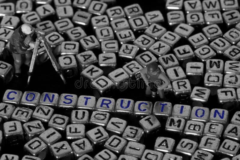 Bokstaven blockerar stavningskonstruktion med modellbyggnadsarbetare arkivfoto