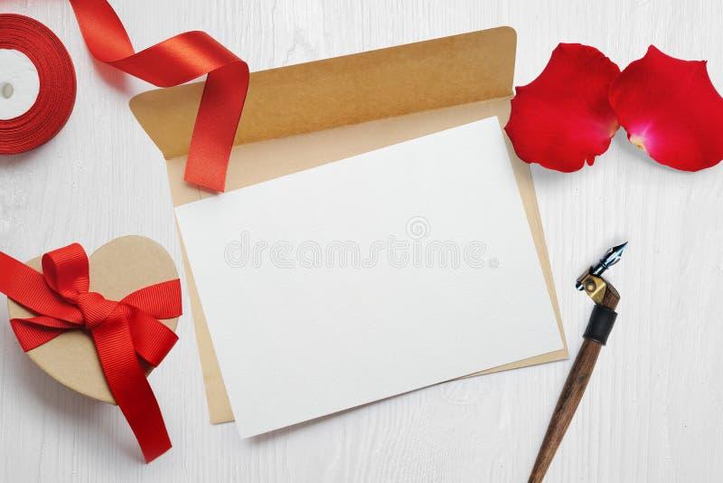 Bokstaven för kortet för hälsningen för modellvalentindagen i kuvert med det röda bandet för den kraft gåvaasken, lägenhet lägger royaltyfri fotografi