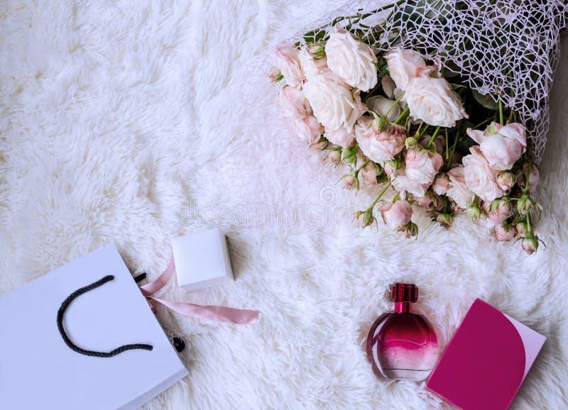 Boksuje z prezentem, torba, perfumy na białym puszystym tle fotografia royalty free