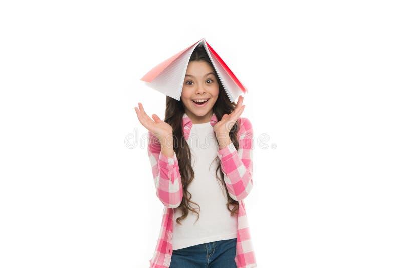 Boktak över hennes huvud Skolflicka som är klar att studera Studie i skola studytid till Vit bakgrund för flickahållbok royaltyfri foto