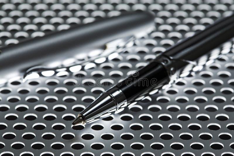 Bolígrafo en la hoja de metal perforada foto de archivo