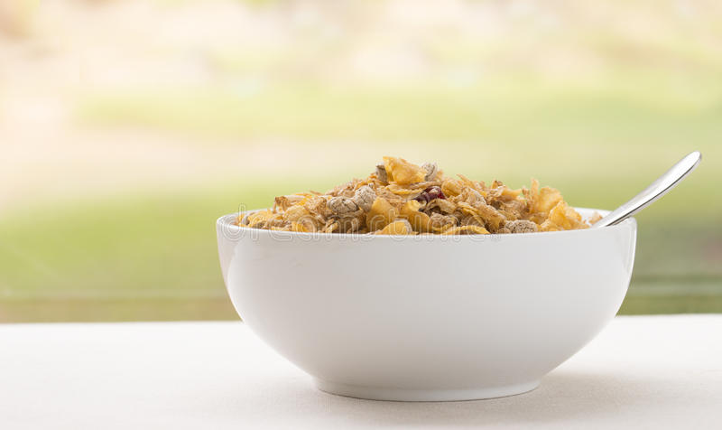 Bol blanc complètement de céréale de petit déjeuner avec la cuillère photos stock
