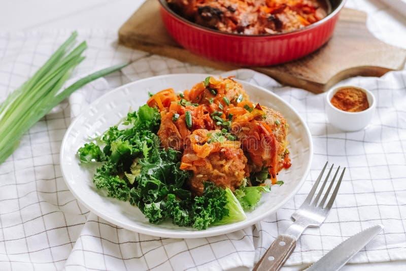Bol blanc de boulettes de viande cuites à la maison avec des légumes et des feuilles de salade photographie stock libre de droits