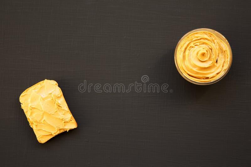 Bol de beurre d'arachide et de pain grillé sur un fond noir, vue supérieure photographie stock