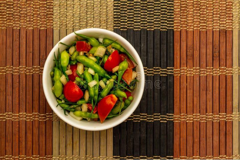 Bol de cosses cuites à la vapeur de graine de radis avec des tomates-cerises photos stock