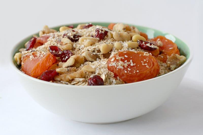 Bol de farine d'avoine avec des noix et des fruits image stock