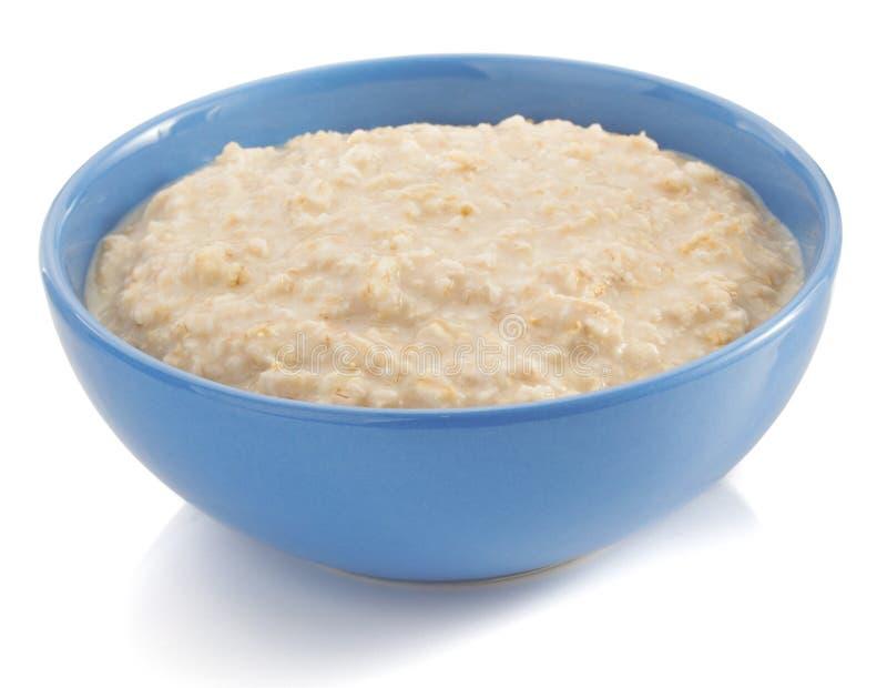 Bol de farine d'avoine sur le blanc photo stock