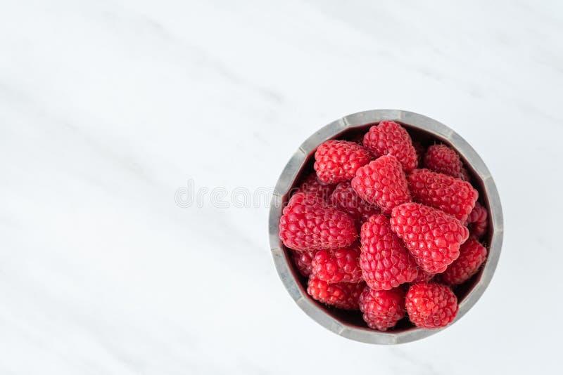 Bol de framboises rouges fraîches pour le dessert, cuvette d'acier inoxydable, fond de marbre blanc images libres de droits