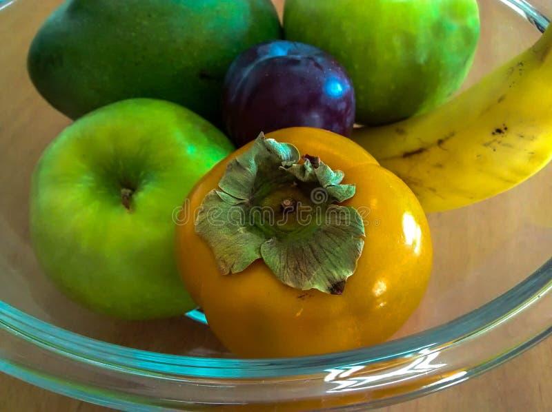 Bol de fruit en verre avec le kaki, les pommes, la banane, la prune et la mangue photos stock