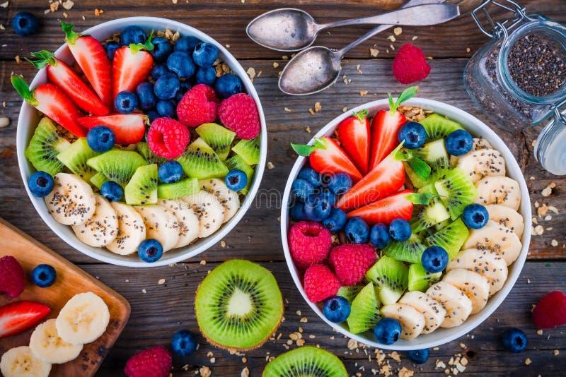 Bol de petit déjeuner : granola avec des graines de banane, de kiwi, de framboise, de fraise, de myrtille et de chia photos stock
