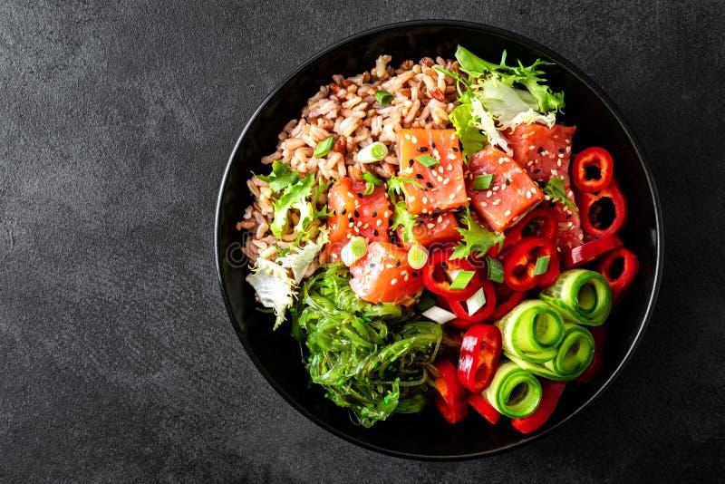 Bol de poussée de riz brun, truite ou filet saumoné, salade d'algue de Chuka, sésame et légumes frais sur le fond foncé images libres de droits