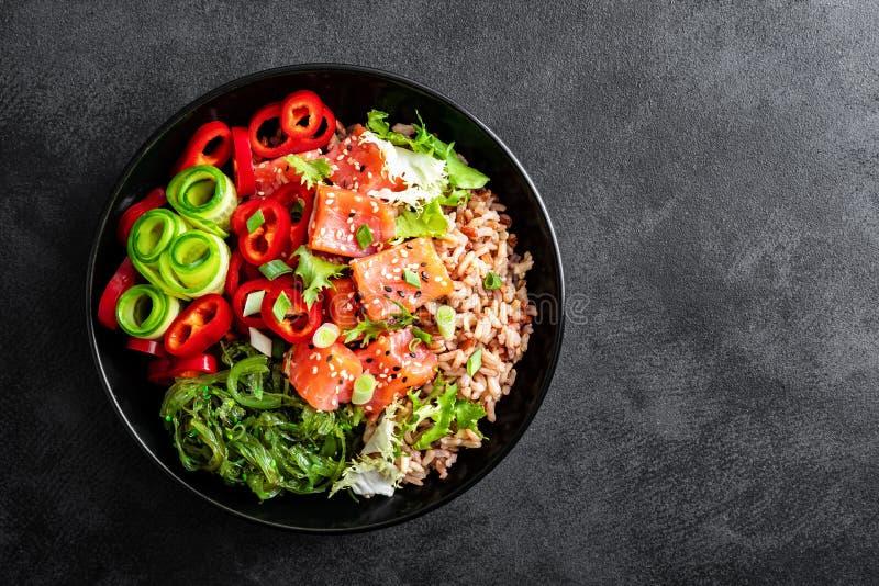 Bol de poussée de riz brun, truite ou filet saumoné, salade d'algue de Chuka, sésame et légumes frais sur le fond foncé image stock