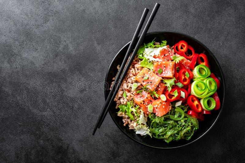 Bol de poussée de riz brun, truite ou filet saumoné, salade d'algue de Chuka, sésame et légumes frais sur le fond foncé photo libre de droits