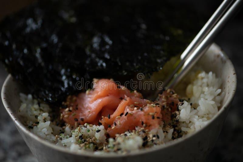 Bol de riz avec les saumons et l'algue photographie stock