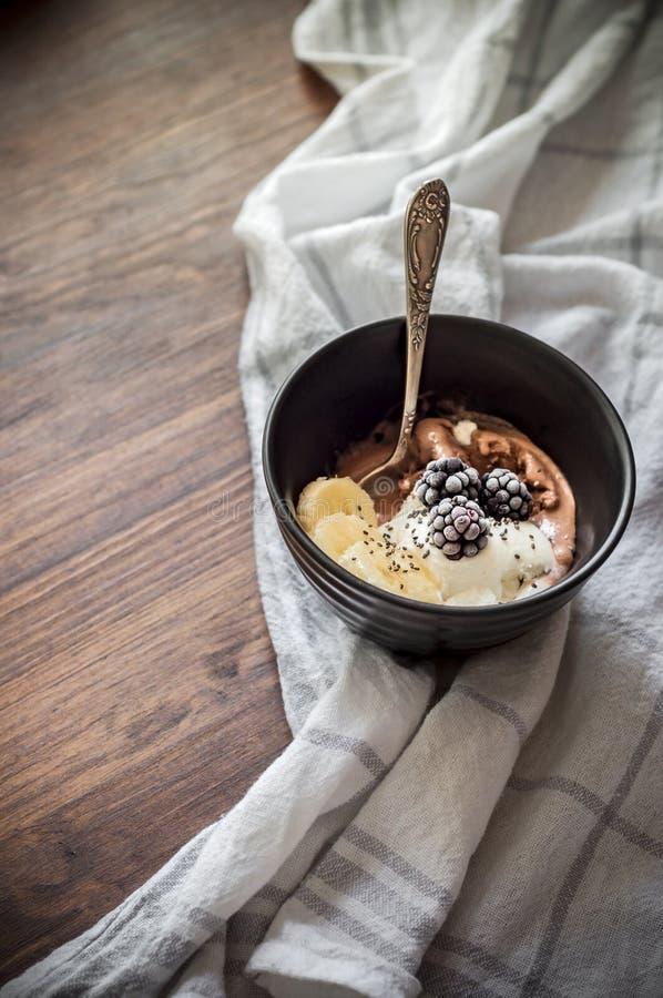 Bol de Smoothie avec la crème glacée de vanille et de chocolat, les mûres, les tranches de banane et les graines de chia sur le f photo stock