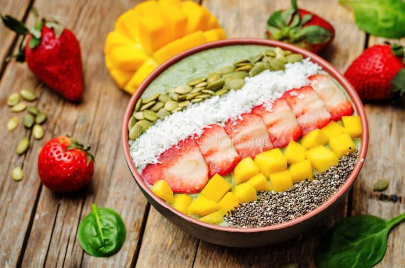 Bol de smoothie d'épinards avec des fraises, noix de coco, mangue, potiron images stock