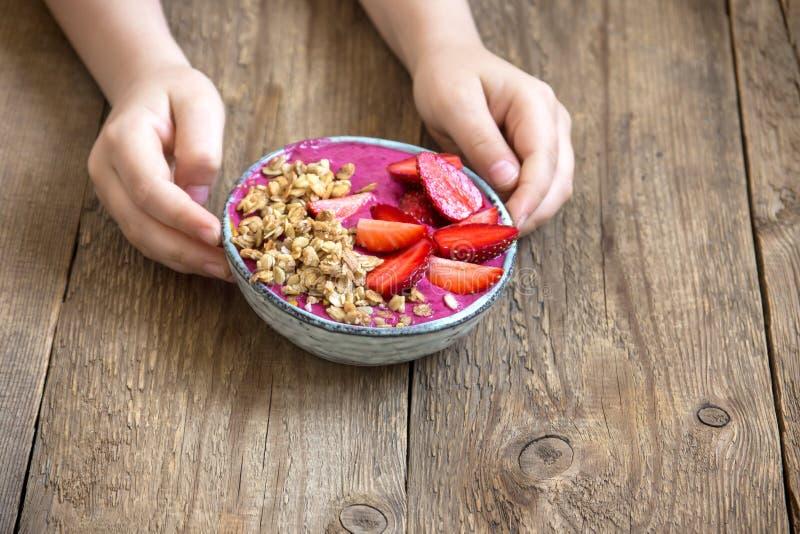 Bol de smoothie de petit déjeuner dans des mains images stock