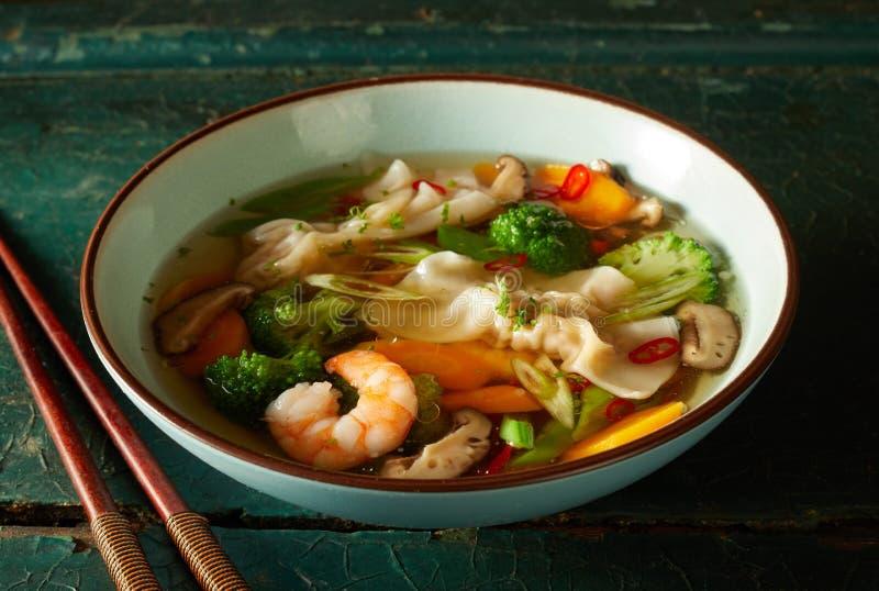 Bol de soupe à wonton orientale savoureuse avec des légumes images stock