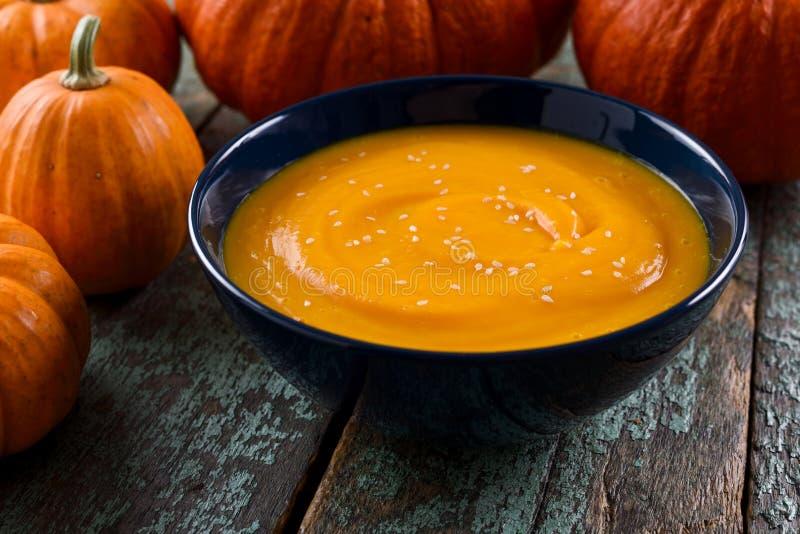 Bol de soupe épicée à potiron de vegan décorée de l'unité centrale lumineuse d'orange images libres de droits