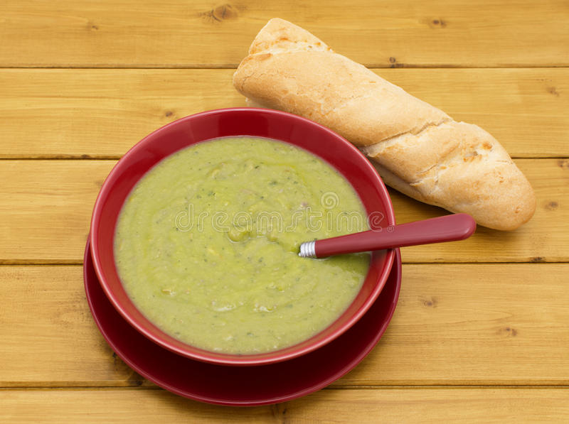 Bol de soupe aux pois et à jambon avec une baguette photo libre de droits