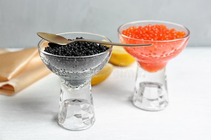Bol de vidrio con el caviar negro y rojo fotografía de archivo