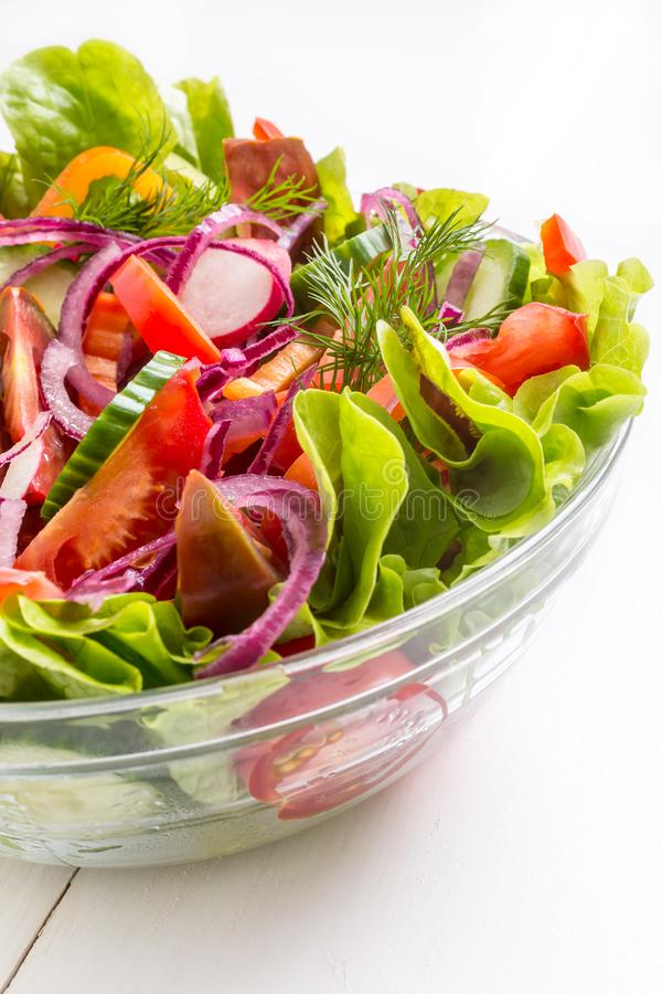 Bol de vidrio con el primer colorido delicioso de la ensalada de las verduras frescas imagen de archivo