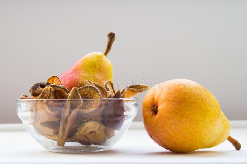 Bol de vidrio con las rebanadas org?nicas secadas hechas en casa de la pera con las peras frescas en el fondo blanco fotos de archivo