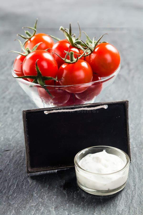 Bol de vidrio de tomates de cereza y de salsa sabrosa foto de archivo