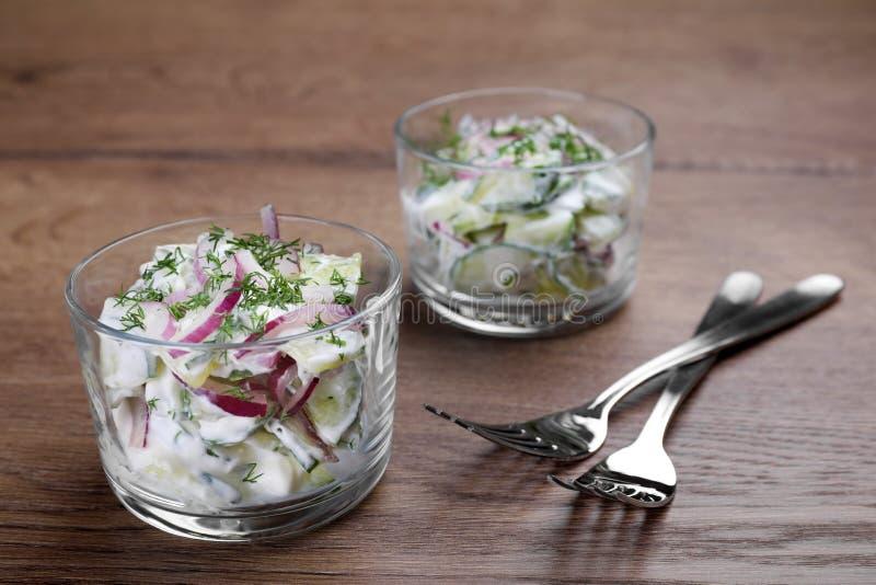 Bol de vidrio de ensalada vegetariana con el pepino y la cebolla fotografía de archivo