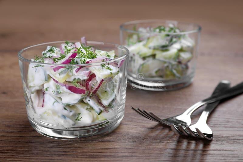 Bol de vidrio de ensalada vegetariana con el pepino y la cebolla en la tabla foto de archivo libre de regalías