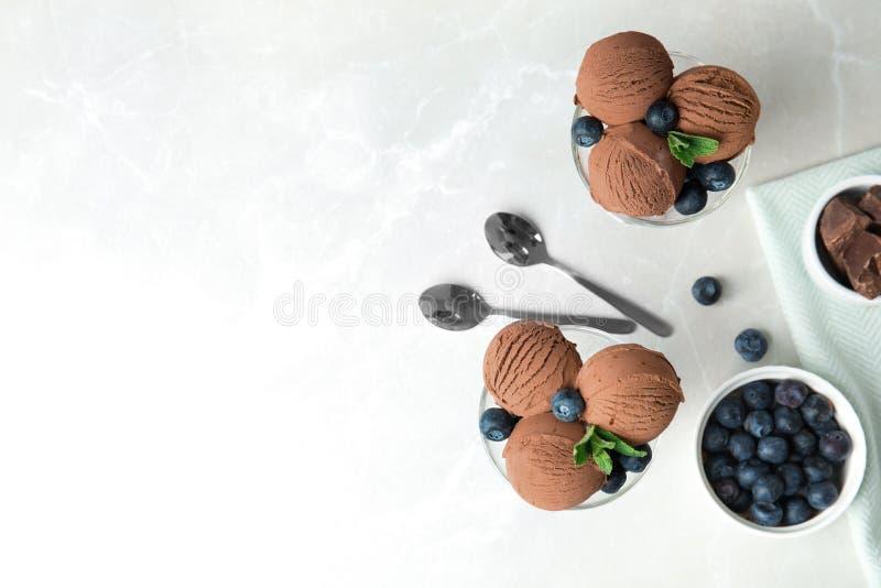 Bol de vidrio de helado y de arándanos de chocolate servidos en la tabla ligera, endecha plana fotos de archivo