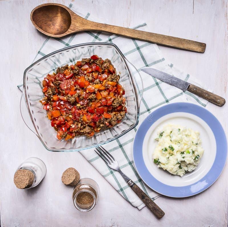 Bol de vidrio menudo de las verduras de la carne picadita cebollas de madera de los purés de patata de una cuchara una placa azul fotografía de archivo libre de regalías